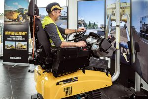 Ein Schulungsteilnehmer erlernt das Bedienen der Baumaschine mit Hilfe des Komatsu-Fahrsimulators.