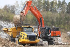 Die Mulden des Bell B45E 4x4-Dumper werden von einem Bagger gefüllt.
