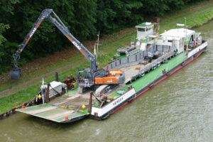Instandhaltung: Der Atlas Kettenbagger 340 LC blue bei Böschungsarbeiten vom Schiff aus